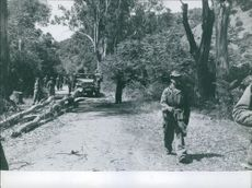 Soldiers on the road with their vehicle.