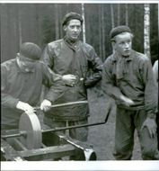 Ake Forsberg sharpens ax accompanied by Gösta Forsell and Bengt Södersten forest boarding.