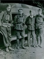 Pierre Marcilhacy standing together with soldiers, looking towards the camera and smiling.