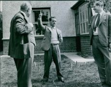 Gordon Richards with other people in front of house, 1954.