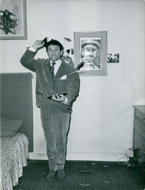 A MAN STANDING IN HIS ROOM