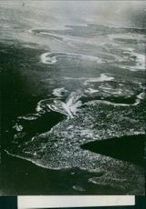 Aerial view of Munda Point, shows smoke rising along the runway of a Japanese air field during a bombing attack by American planes.