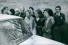 People standing and looking in the car, surprised. 1969
