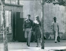 Horst Buchholz and wife Myriam Bru holding hands while walking.