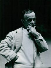 Italian designer Emilio Schuberth is watching something, while he hold up a cigar