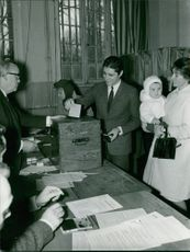 """Alexandre """"Sacha"""" Distel with his wife, Francine Distel while putting a paper in the box, 1965."""