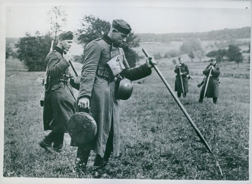 Soldiers looking for mines in the grassy fields.