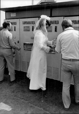 The newlywed bride buys a lemonade before she and her husband go up to the Lenin Heights to see Moscow from above.