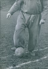 Man playing football in the ground, kicking. 1945