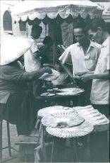 A vintage photo of people in Vietnam during war some still continue their business on streets.