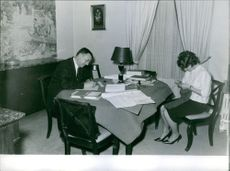 1961  A photo of a  man and woman sitting in the drawing room, doing their activity.