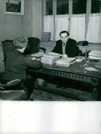 Pierre Mendes France discussing with a woman on his desk.