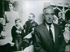 Portrait of a British statesman and naval officer Louis Mountbatten standing against family poster. 1970