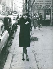Anne-Marie Bellini posing for the camera in the sidewalk.