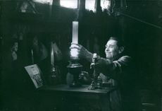 Man lighting a lamp.