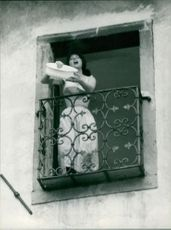 Silvana Mangano standing in balcony, pouring water below.