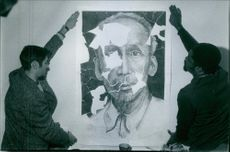 People applying ruined poster of Ho Chi Minh on the wall.