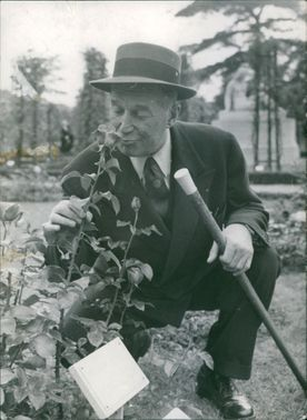 Maurice Auguste Chevalier looking at plants.