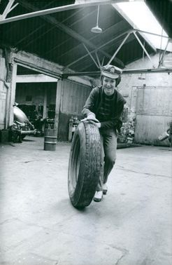 A LADY PULLING OUT A TYRE