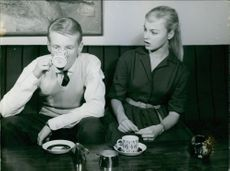 """A young man drinking tea, sitting beside a woman who's looking at him surprisingly.   """"__ Lillemor"""""""