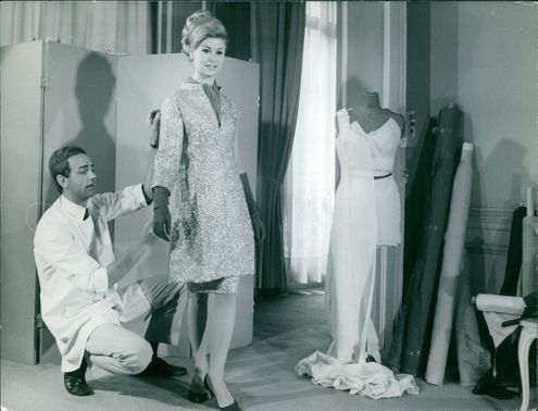 Miss Europe 1965, Juliana Herm smiling at the camera while a man from behind her is fixing her dress. 1965
