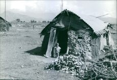 A child stepping out of their shanty house.