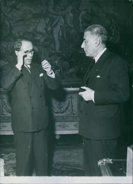 Antoine Pinay standing and talking to a man.