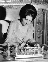 Farah Pahlavi writing at her desk.