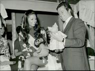 Monique Blake and Roger Moore are looking at things for sale on the YMCA market