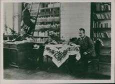 """Military Leader sitting in an office chair inside the library.  """"German west __"""""""