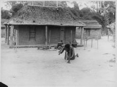 A man kneeling down on the ground outside his house.