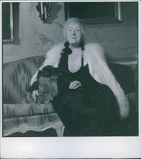 Anna Branting sitting on sofa with her pet dog.