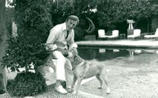Kirk Douglas with his dog in his home in Beverly Hills