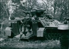 A soldier in full combat gear runs from a Marder personnel carrier. 1977.