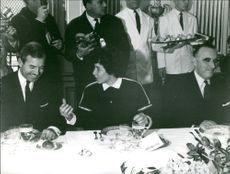 Goitschel speaking to a male guest during lunch, 1964.