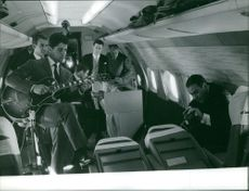 A group of musicians playing inside a plane, 1959.