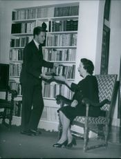 Woman sitting on chair, man standing beside giving her a book.