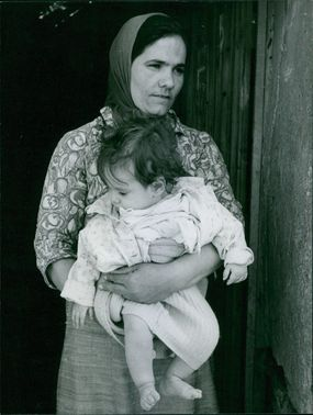 Vintage photo of a woman wearing a scarf on her hair and carrying her baby.