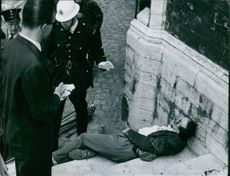 A victim of criminal abuse lying on stairs, cop investigating. Photo taken on July 3, 1959.