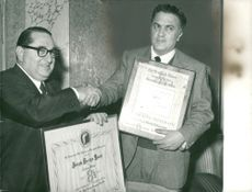 """Portrait image of Frederico Fellini with one of the prizes he received for the movie """"8 1/2""""."""