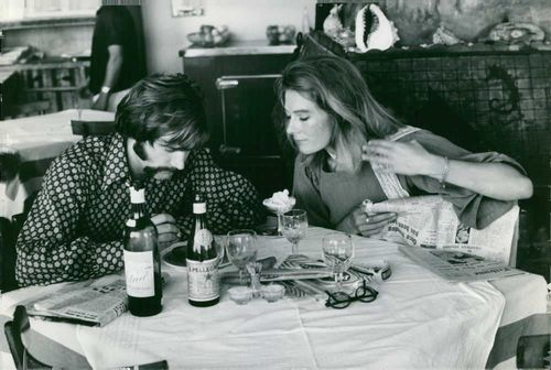 Franco Nero and Vanessa Redgrave looking at something at dinning table.