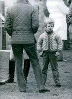 Peter Phillips standing with his parents and looking a little bored at the horsey goings-on during the Badminton Horse Trials. 1983.