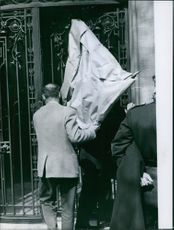 Roland Peugeot entering inside together with another man carrying a parcel at the time when his son Eric, was kidnapped. Photo taken on April 19, 1960.