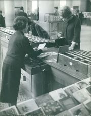 Princess Beatrix of the Netherlands browsing for post cards inside a bookstore.