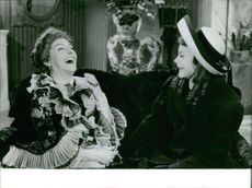 Two women laughing together.  - Jul 1964