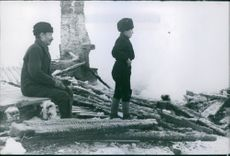 Wreckage after the bombing, with a man and a boy, during Winter War, 1940.