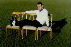 Football coach Nisse Andersson poses lying on three chairs on the pitch.