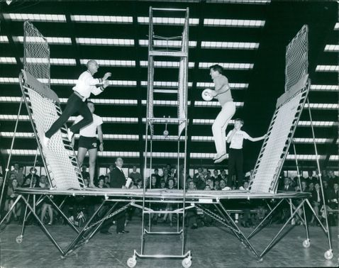 Two men playing ball in a trampoline.