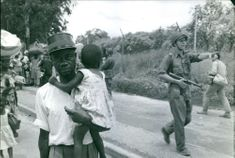 Man holding child, soldier patrolling in Kongo.