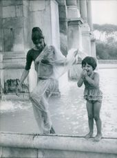 Amina Roshan photographed having fun at the fountain with a young girl. 1962.